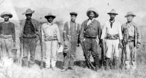 Mex ev 1910 Julio Rodriguez (at center, holding camera) in Mexico with revolutionary fighters, circa 1910.